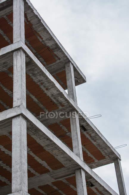 Vista de ángulo alto de inacabada construcción con estructura de hormigón sobre cielo azul - foto de stock