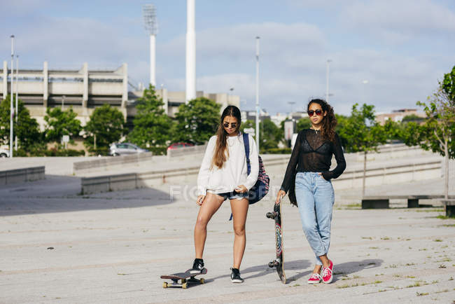 Trendy girls on skateboards — Stock Photo