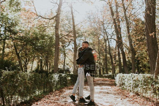 Vista lateral do casal romântico abraçando no beco do parque — Fotografia de Stock