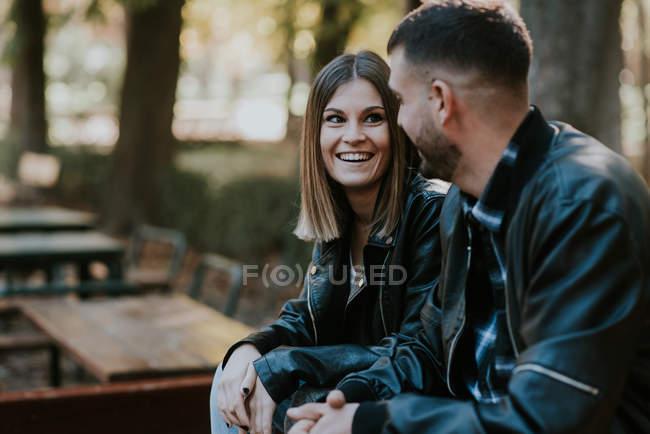 Retrato de dos jóvenes sonriendo y hablando en el parque - foto de stock