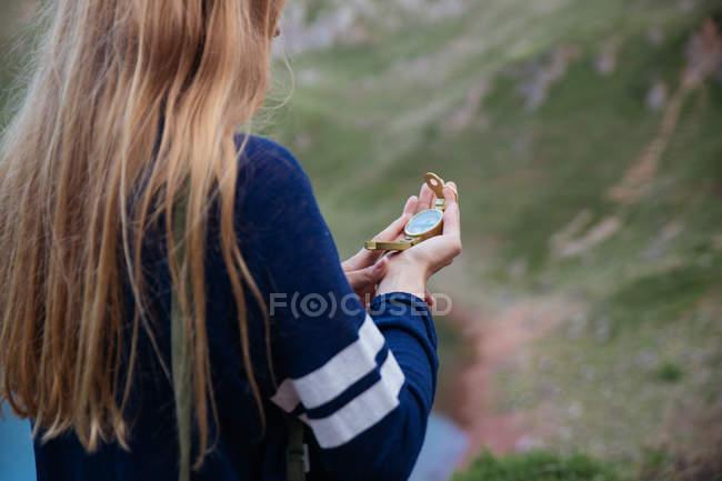 Vista posteriore della ragazza che esamina bussola in mano alla campagna montagna — Foto stock