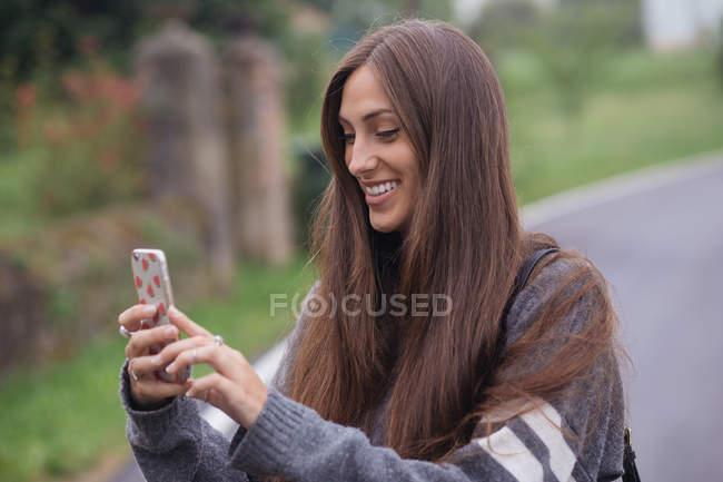 Femme souriante utilisant un smartphone sur la route à la campagne — Photo de stock
