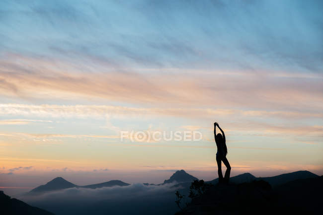 Silhouette of woman cheering sunset on mountain top against of amazing sky — Stock Photo