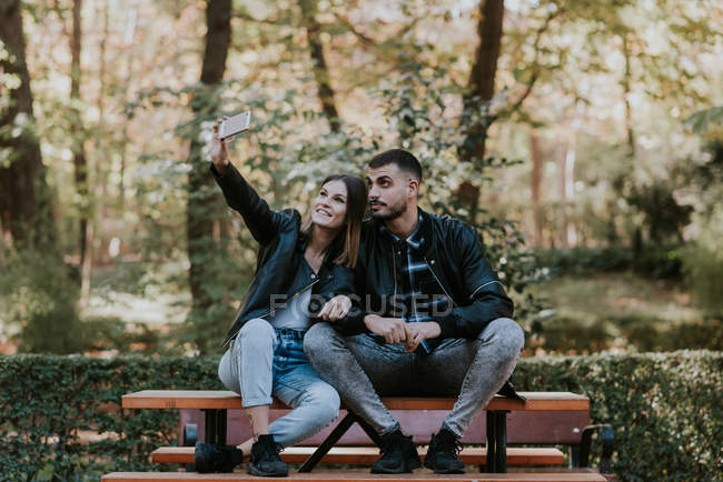 Jeune couple assis sur la table du parc et prise selfie — Photo de stock