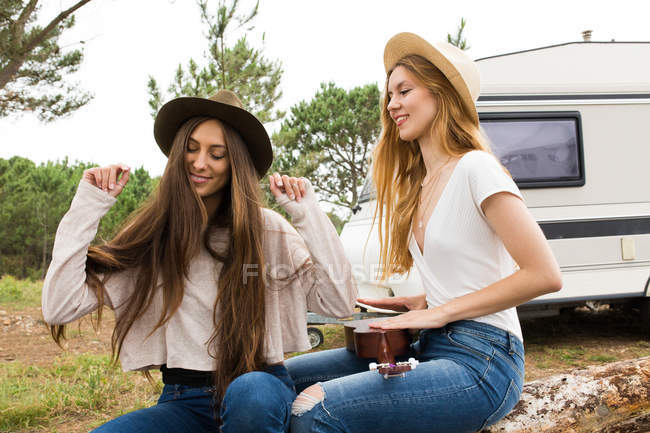 Girls having fun with playing ukulele — Stock Photo