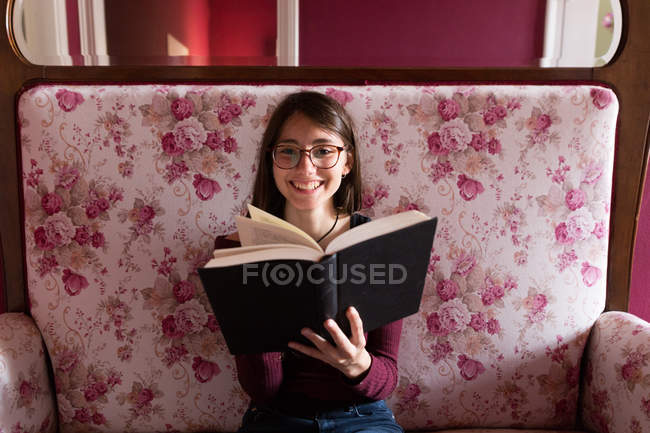 Smiling female with book on couch — Stock Photo