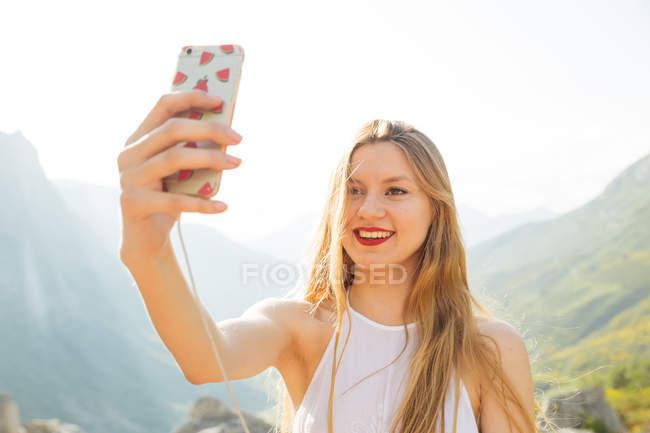 a75335cb2 Retrato de mujer con pelo largo Rubio haciendo selfie con smartphone sobre  montañas de telón de
