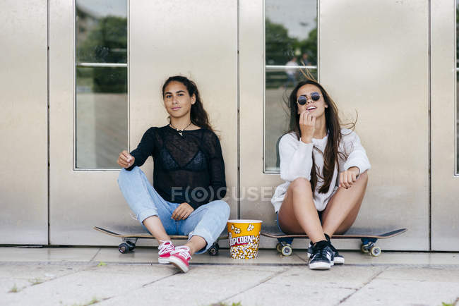 Stylish teens with popcorn on skates — Stock Photo