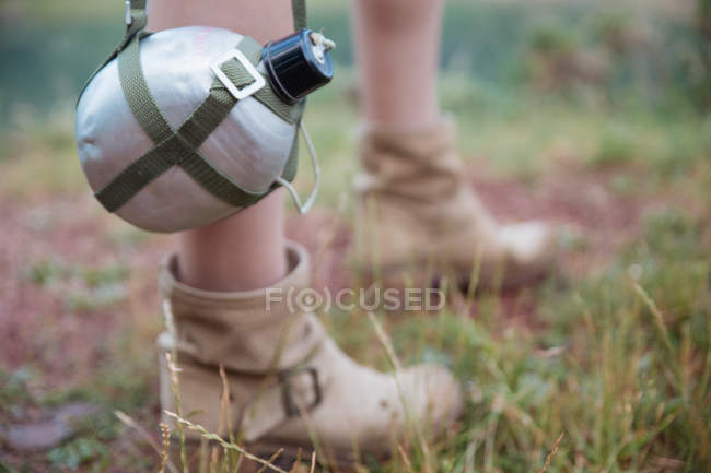 Close-up of touristic flask hanging on strap by female legs — Stock Photo