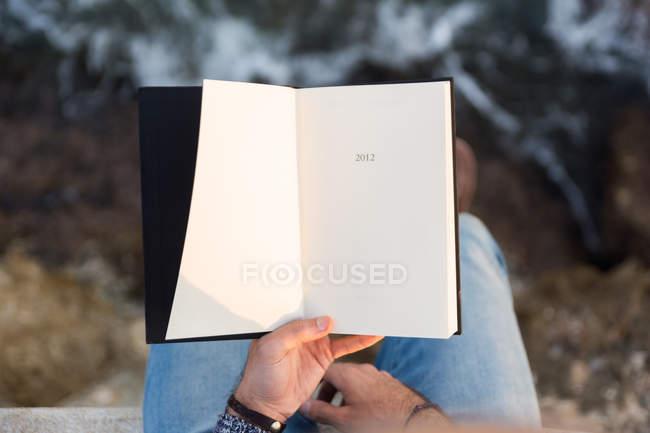 Schnappschuss einer männlichen Hand in Pullover mit Notizbuch im Hintergrund — Stockfoto