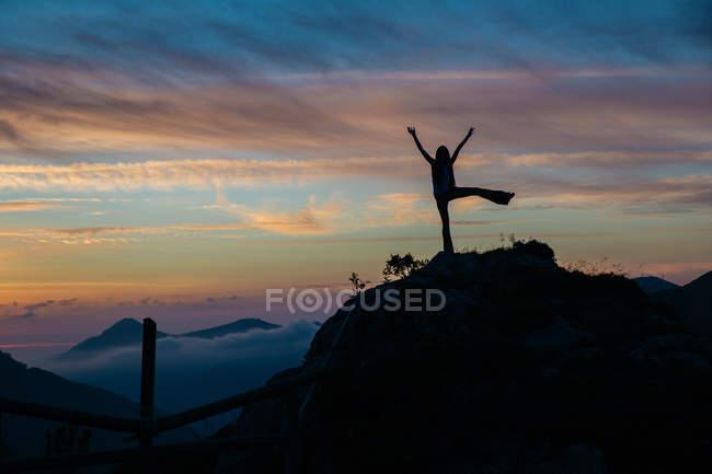 Silueta de mujer con brazos y piernas posando sobre el pico de la montaña sobre el crepúsculo cielo sobre fondo - foto de stock