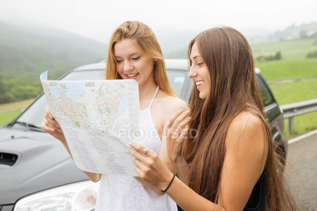 Portrait of two girls standing beside car and looking at map — Stock Photo