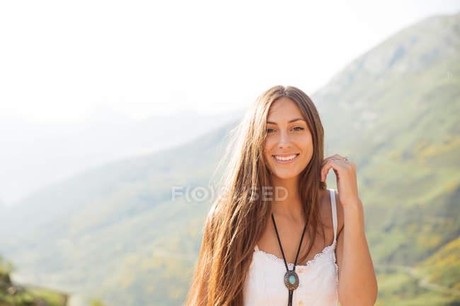 Девушка в белом платье, регулируя волос — стоковое фото