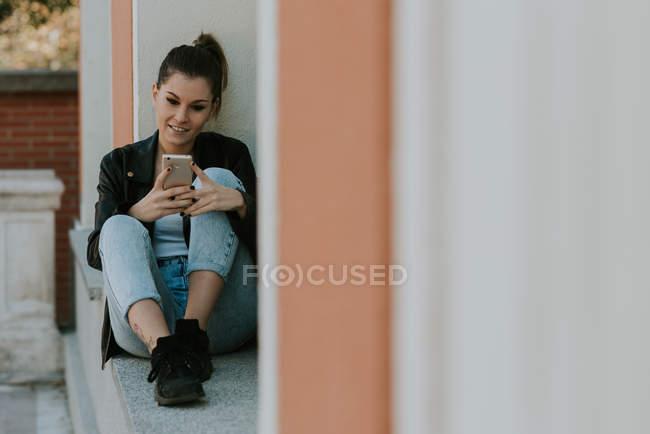 Jeune fille assise sur le rebord de la fenêtre et tapant sur smartphone — Photo de stock