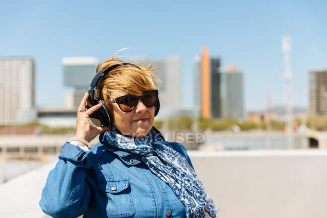 Mujer mayor disfrutando de los auriculares - foto de stock