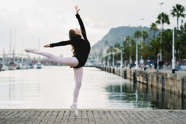 Young gymnast in pose at waterfront — Stock Photo
