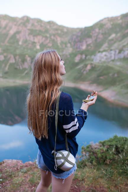 Girl using compass at mountain lake — Stock Photo