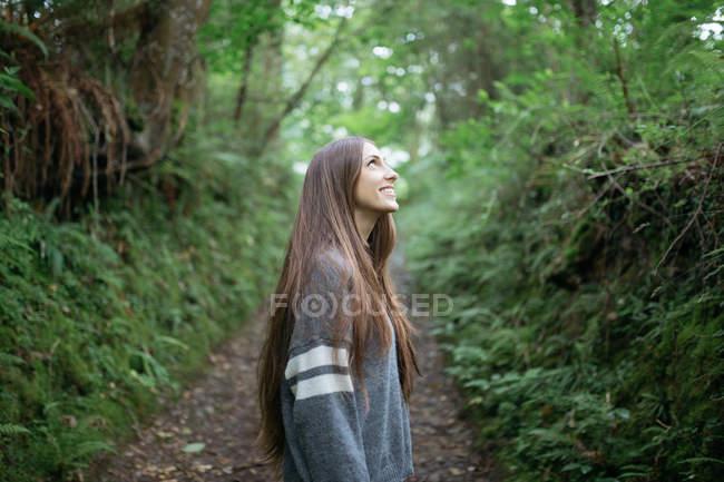 Jeune fille souriante au chemin forestier — Photo de stock