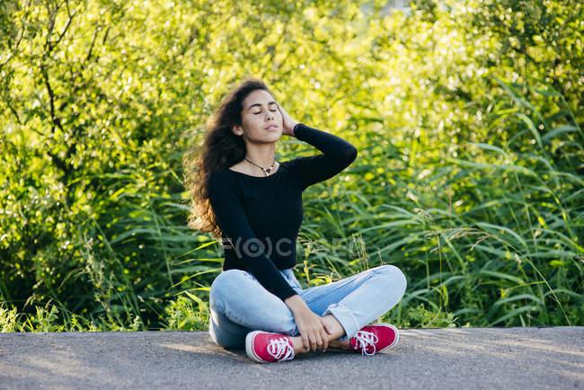 Belle jeune fille assise sur le sol — Photo de stock