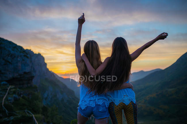 Two girls hugging over mountain sunset — Stock Photo