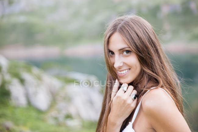 Smiling brunette girl in white dress posing at mountain lake — Stock Photo