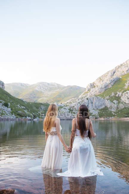 Задній вид bwomen в білих сукнях, стоячи в гірському озері — стокове фото