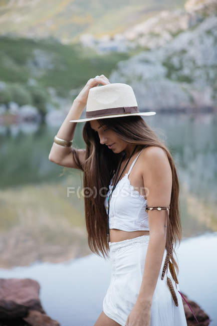 Portrait of happy brunette woman in hat posing against of mountain lake — Stock Photo