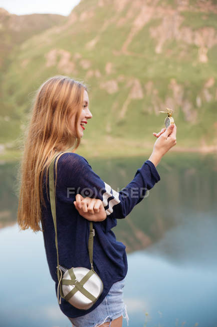 Vista laterale della ragazza bionda con la boccetta d'attaccatura sulla spalla guardando la bussola in mano sopra il lago su priorità bassa — Foto stock
