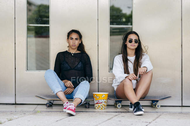 Adolescentes con estilo con palomitas de maíz en patines - foto de stock