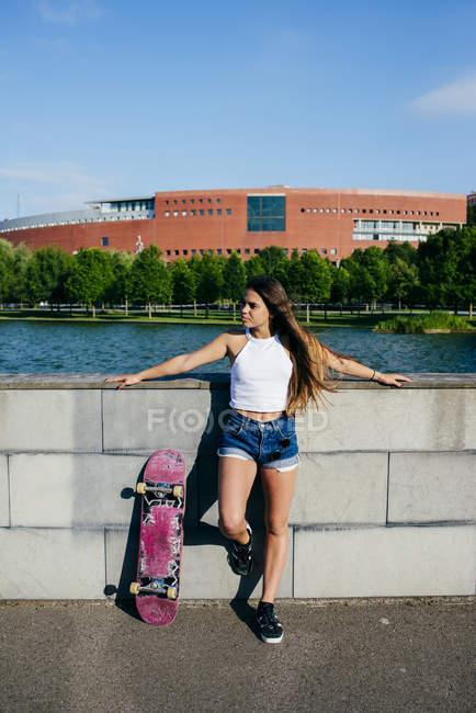 Стильный подросток позирует со скейтом — стоковое фото