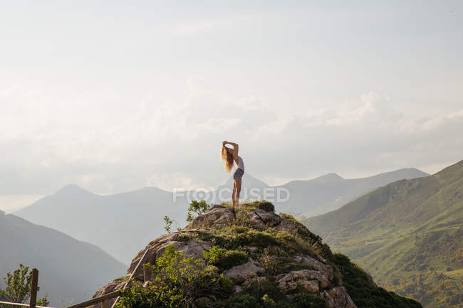 Side view of woman posing against of landscape of mountains and clouds in sky — Stock Photo