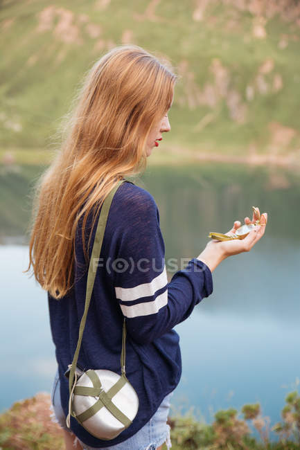 Vista laterale di giovane ragazza guardando la bussola con la boccetta sulla spalla nel lago della montagna — Foto stock