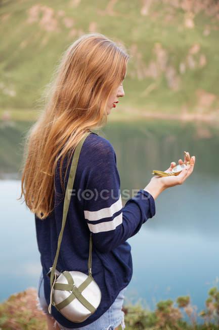 Vista lateral da menina olhando a bússola com balão no ombro no lago de montanha — Fotografia de Stock