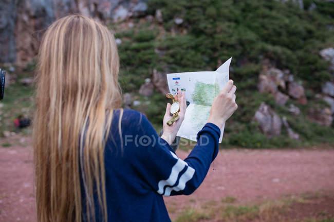 Девушка с помощью компаса и карты на горной дороге — стоковое фото