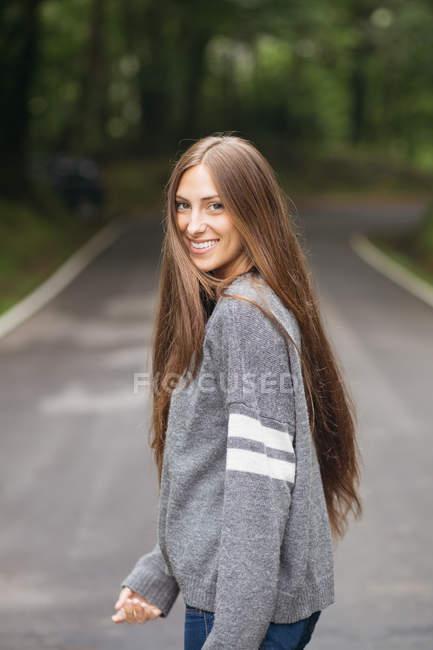 Morena chica de pie en la carretera y mirando por encima del hombro a la cámara - foto de stock