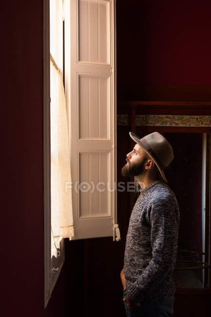 Young man in hat near window — Stock Photo