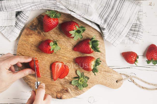 Mulher mãos cortando morangos — Fotografia de Stock