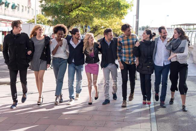 Caminando en línea colegas abrazándose en la calle y mirándose el uno al otro - foto de stock