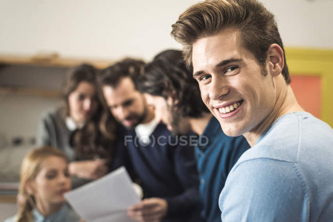 Cheerful man looking at camera over business people working on background — Stock Photo