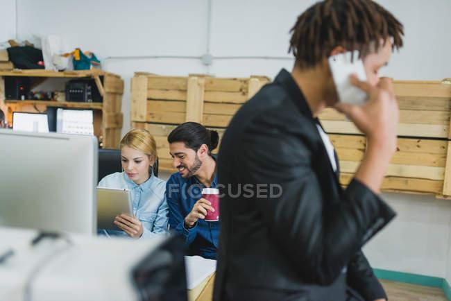 Scena di ufficio di uomo e donna che navigano tablet mentre il collega parla telefono — Foto stock