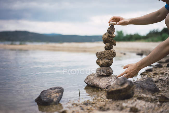 Male hands making stone tower at shore on cloudy day — Stock Photo