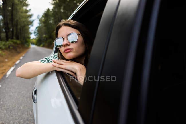 Ragazza elegante guardando fuori dal finestrino dell'auto — Foto stock