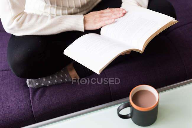 Crop image of female sitting with crossed legs on coach and reading book — Stock Photo