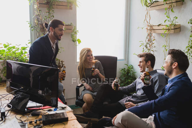 Side view of happy people drinking beer at workplace in office — Stock Photo