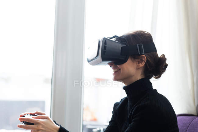 Side view of brunette girl wearing virtual reality glasses and playing video game with gamepad — Stock Photo