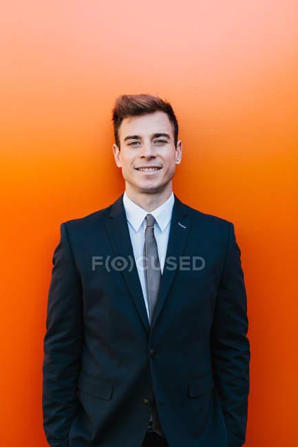 Glücklicher Geschäftsmann posiert gegen orangefarbene Wand — Stockfoto