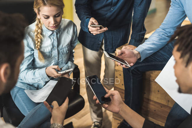 Multi-ethnic business people using smartphones at meeting in office — Stock Photo