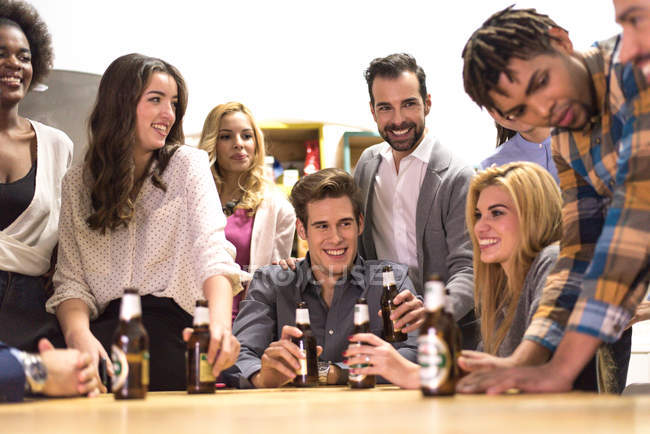cheerful colleagues talking to each other with beer bottles in hands