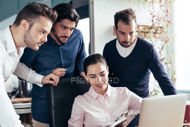 Businesswoman cooperating with colleagues at workplace in modern office — Stock Photo