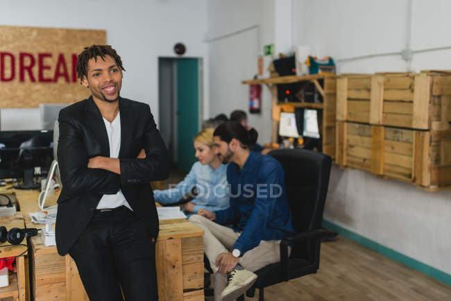 Portrait of smiling businessman leaning on table and looking away at office — Stock Photo